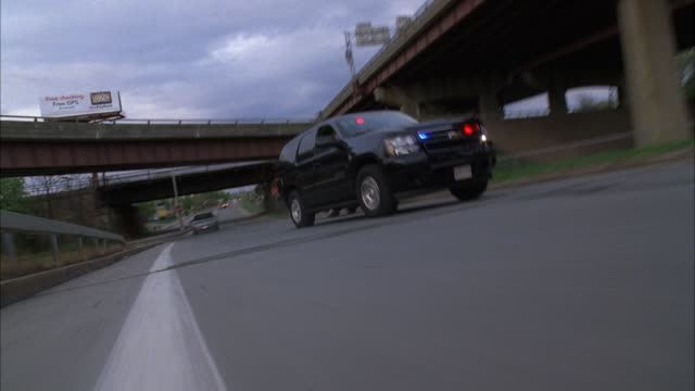 tracking shot of police suv, chevrolet tahoe, driving on freeway or highway. speeding, swerving between cars. flashing lights. could be part of car chase. car stunt. - stunt stock-videos und b-roll-filmmaterial