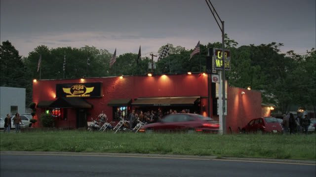 "wide angle of bar or pub next to car wash parking lot. motorcycle gang visible in bg standing at entrance to bar. cars drive by in fg. could be freeway or highway. american flags fly atop bar. neon signs in window. sign above bar reads ""jugs."" - motorcycle biker stock videos & royalty-free footage"