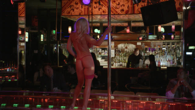 medium angle of a blond stripper in a dark and seedy strip club. red g-string and tassels.  large fake breasts.  she dances around a stripper pole. a businessman watches her, dollar bills in hand. patrons at the bar in the background. - strip stock-videos und b-roll-filmmaterial