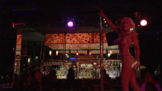 vidéos et rushes de medium angle of a blond stripper in a dark and seedy strip club. red g-string and tassels.  large fake breasts.  she dances around a stripper pole. a businessman watches her while drinking a beer. patrons at the bar in the background. - peep show