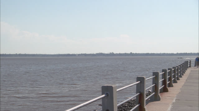 PAN LEFT TO RIGHT FROM WATER, LAKE PONTCHARTRAIN, AND BIKE PATH OR WALKING TO PARK WITH MONUMENT IN CENTER. PEOPLE WALKING DOG THROUGH THE PARK.