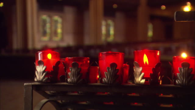 est close angle. five lit prayer candles lined up in a row inside a cathedral. see church pews and stained glass windowns in bg. - church stock videos & royalty-free footage