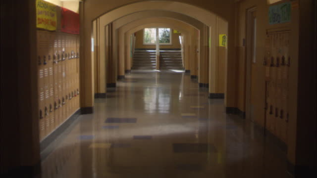 est wide angle hallway inside school building. lockers aligned along hallway.  stairway at end of hallway. zoom in on students walking across  hallway. - corridor stock videos & royalty-free footage