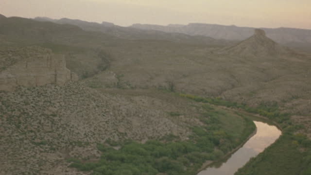 high angle down of white single engine propeller plane flying over rocky mountainous terrain. see pink and orange sky. see some green on mountains below. see small river below as plane dips close to desert landscape. - propeller video stock e b–roll