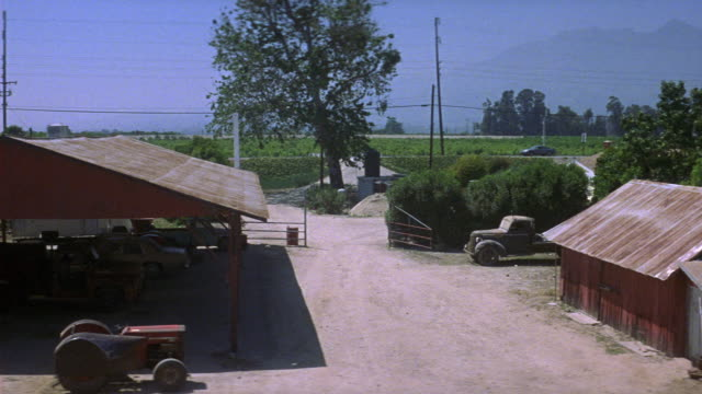 wide angle down of farm and farmhouses. see dirt road in middle of farm. see gray ford taurus drive from dirt road in background through open gates of farm and park next to other trucks. see tractor parked in foreground. - other stock videos & royalty-free footage