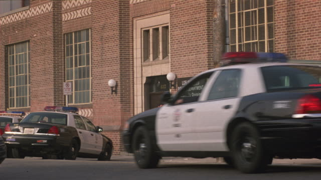 medium angle of los angeles police station during day. see police cars and police motorcycles parked outside. see police officers walking around outside. see police car pull up and two officers get out and walk into building. - police car stock videos and b-roll footage
