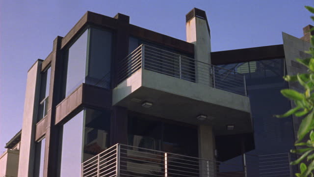 up angle of modern multi-story upper class house. could be beach house. see floor-length windows on all floors and brown trim. see beige balconies with metal railings. see green leaves of plant in right foreground. see clear blue sky. dx/nx matching.<p><a - floor length stock videos & royalty-free footage