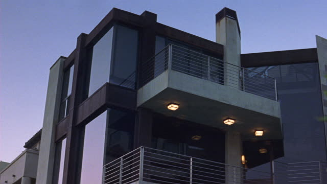 up angle of modern multi-story upper class house. could be beach house. see floor-length windows on all floors and brown trim. see beige balconies with metal railings. see green leaves of plant in right foreground. see lights on above lower balcony. dx/nx - floor length stock videos & royalty-free footage