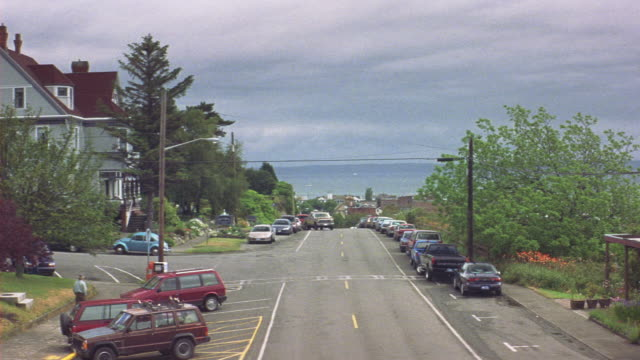 medium angle of two lane suburban city street. see ocean and low hanging clouds in background. see cars parked along sides of street and traffic moving toward pov. see gray three story house or mansion with red roof at left. pan down left to see brown two - stone house stock videos & royalty-free footage