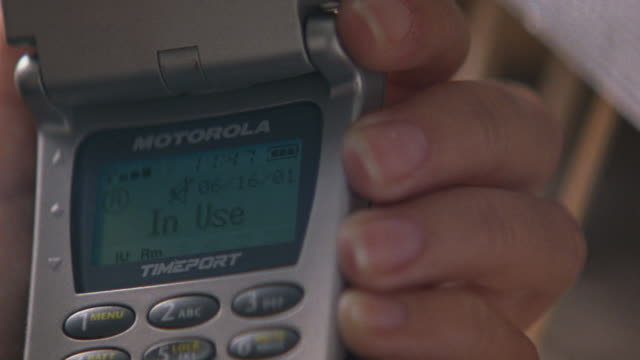 """CLOSE ANGLE OF LEFT HAND HOLDING MOTOROLA TIMEPORT FLIP CELL PHONE. SEE SCREEN READ """"06/16/01 IN USE"""". SEE TIME READING """"11:47"""" AND SIGNAL BARS FLUCTUATE. SEE SCREEN READ """"SIGNAL FADED CALL LOST"""". SEE PHONE SNAPPED SHUT."""