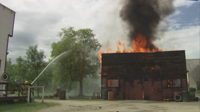 wide angle of firefighters or firemen with hoses extinguishing building on fire. men start by spraying tree next to building with water, then spray building until flames die down. smoke and steam rise from building. small town. fire action. metal oil drum - stahlfass stock-videos und b-roll-filmmaterial