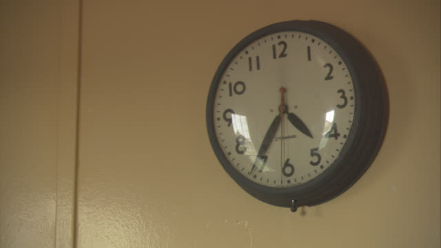 vídeos y material grabado en eventos de stock de close angle of old wall clock on yellow wall. hands are stuck at 4:36. reflection from window on clock face. - pared