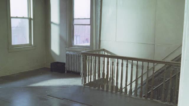 medium angle of empty loft or apartment. hardwood floors and stair banister or railing. heater or radiator under window. - loft stock-videos und b-roll-filmmaterial