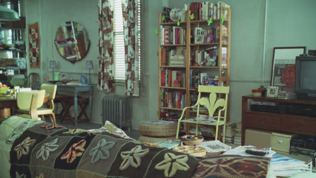 medium angle of apartment. could be young couple's loft. bookshelves, television, couch, chairs. room cluttered. living room. - regal stock-videos und b-roll-filmmaterial
