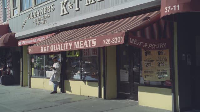 "medium angle of store front in new york. butcher shop or meat shop. cleaners and alterations next door. awnings on storefronts or shops. sign on awning ""k & t quality meats."" - butcher stock videos & royalty-free footage"