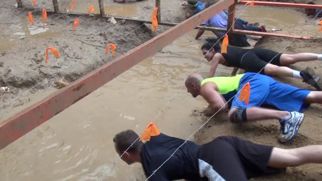obstacle racers through mud - hindernisparcours stock-videos und b-roll-filmmaterial