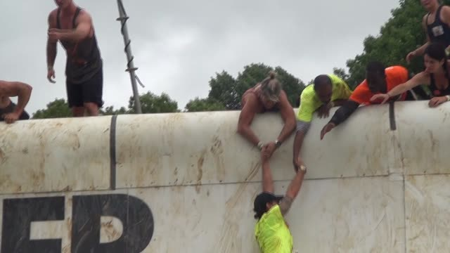 obstacle racer up steep ramp helped by teammates - salmini stock videos and b-roll footage