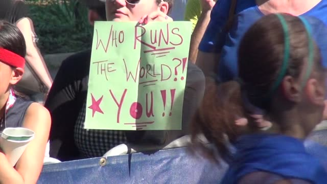 CLEVER SIGNS HELD BY SPECTATORS AS RUNNERS GO BY