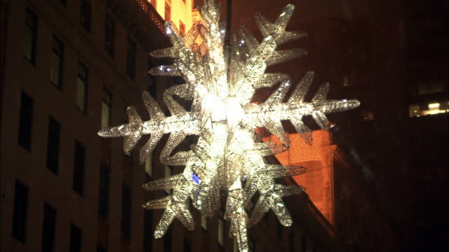 UP ANGLE OF SNOWFLAKE DECORATION HANGING ABOVE INTERSECTION AT 5TH AVENUE AND 57TH. SKYSCRAPER OR HIGH RISE BUILDING IN BG. CROWN BUILDING. CHRISTMAS LIGHTS. UPPER CLASS SHOPPING AREA. IN AND OUT OF FOCUS. SNOWING. MIDTOWN MANHATTAN.
