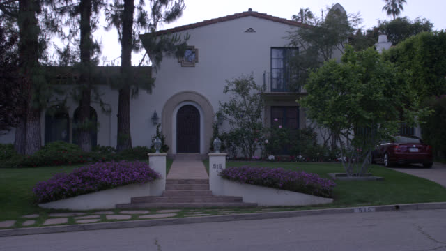 zoom in on front door or entrance to middle to upper class spanish-style two story house. red tile roofs. flowers, trees, bushes and shrubs in front yard or garden. grass lawn. - 2000s style点の映像素材/bロール