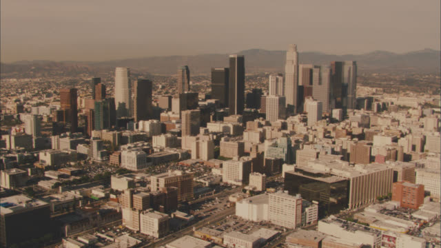 stockvideo's en b-roll-footage met aerial zoom in over downtown los angeles skyline. cities. us bank tower visible. high rises and skyscrapers. mountains in bg. - us bank tower