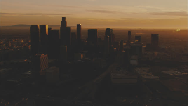 stockvideo's en b-roll-footage met aerial of downtown los angeles city skyline at sunset. high rises and skyscrapers. mountains in bg. us bank tower. office buildings. - us bank tower