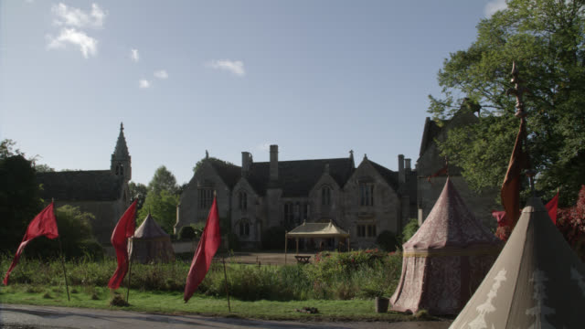 """wide angle of upper class stone building, house, estate or mansion. manor house in great chalfield, wiltshire, england. red flags waving and tents in fg. countryside or rural area.<p><a href=""""https://www.sonypicturesstockfootage.com/footage?kid=4338"""">for - https点の映像素材/bロール"""