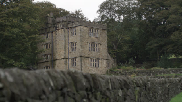 wide angle of three story upper class stone house, estate, or manor. stone wall. trees. countryside. rural area. could be part of castle, crenellation on roof. - stone house stock videos & royalty-free footage