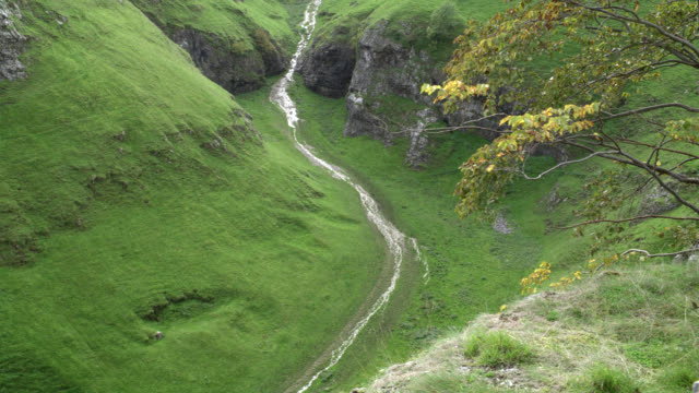 high angle down of woman riding on horseback through valley between grass-covered mountains or hills on path or trail. countryside. rocky cliffs. - cliff video stock e b–roll