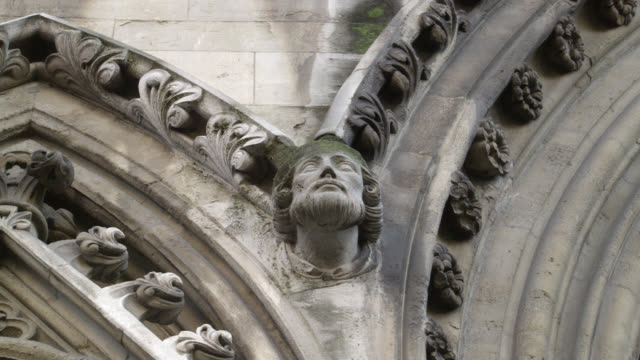 CLOSE ANGLE OF STATUE, CARVING, OR HEAD OR GROTESQUE ON STONE BUILDING. COULD BE CHURCH OR CATHEDRAL. WESTMINSTER ABBEY.