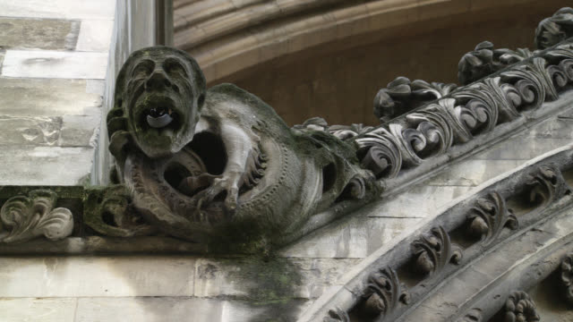 CLOSE ANGLE OF STATUE, CARVING, HEAD, GARGOYLE OR GROTESQUE ON STONE BUILDING. COULD BE CHURCH OR CATHEDRAL. WESTMINSTER ABBEY.