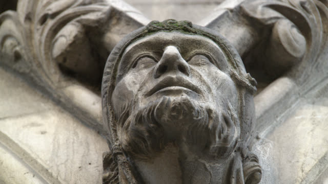 UP ANGLE OF STATUE, HEAD, CARVING, OR GROTESQUE ON STONE BUILDING. COULD BE CHURCH OR CATHEDRAL. WESTMINSTER ABBEY. ARCHITECTURE.