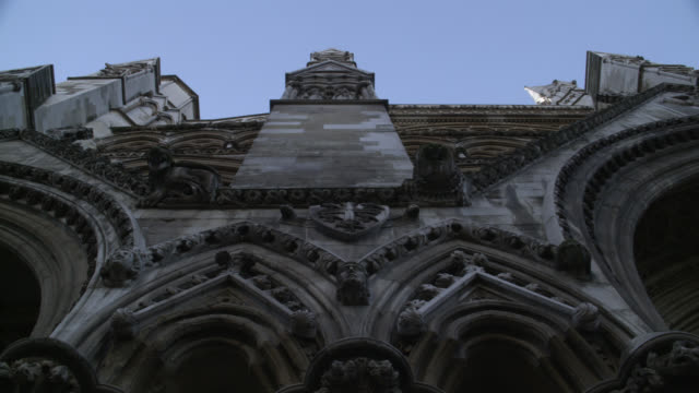 UP ANGLE OF WESTMINSTER ABBEY, GOTHIC CHURCH OR CATHEDRAL. STONE BUILDING. GOTHIC ARCHES WITH ORNATE DECORATIONS OR CARVINGS. GARGOYLES OR GROTESQUES. ARCHITECTURE.