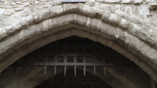 UP ANGLE OF IRON GATE OR PORTCULLIS WITH SPIKES. COULD BE ON MEDIEVAL CASTLE, FORTRESS OR DUNGEON. STONE BUILDING. GOTHIC ARCH.