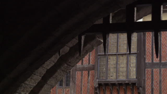 MEDIUM ANGLE POV FROM UNDER A RAISED IRON GATE OR PORTCULLIS WITH SPIKES OF RED BRICK BUILDING IN BG. COULD BE ON MEDIEVAL CASTLE, FORTRESS OR DUNGEON. STONE BUILDING.