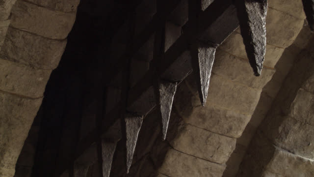 close angle pov from under a raised iron gate or portcullis with spikes. could be on medieval castle, fortress or dungeon. stone building. - tor konstruktion stock-videos und b-roll-filmmaterial