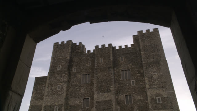 UP ANGLE OF MULTI-STORY STONE BUILDING OR CASTLE WITH CRENELLATION ALONG ROOF. COULD BE FORTRESS. DOVER CASTLE IN KENT. POV FROM UNDER DOORWAY OR ARCHWAY.