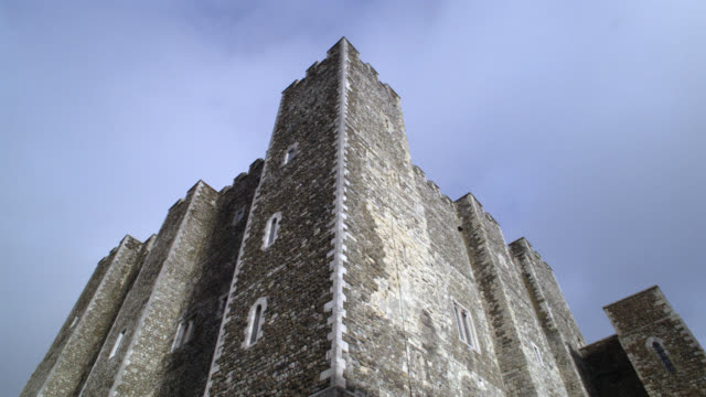 UP ANGLE OF TOWERS ON STONE BUILDING OR CASTLE WITH CRENELLATION ON ROOF. COULD BE FORTRESS. DOVER CASTLE IN KENT.