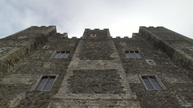 UP ANGLE OF WINDOWS IN STONE BUILDING OR CASTLE WITH CRENELLATION ON ROOF. COULD BE FORTRESS. DOVER CASTLE IN KENT.