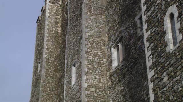 UP ANGLE OF WALLS OF STONE BUILDING OR CASTLE WITH CRENELLATION ON ROOF. COULD BE FORTRESS. DOVER CASTLE IN KENT.