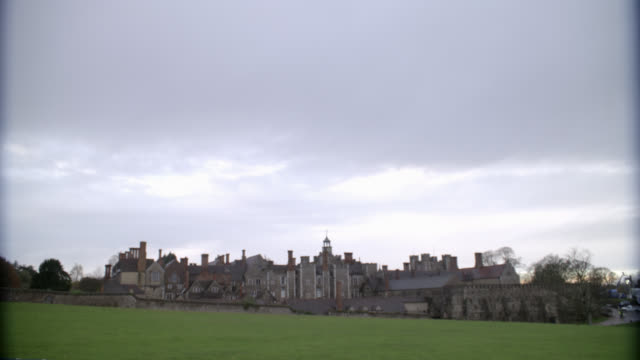 """wide angle of stone buildings of castle, palace or fortress. grass field, lawn or meadow in fg. could be estate. knole at sevenoaks in kent. countryside or rural area.<p><a href=""""https://www.sonypicturesstockfootage.com/footage?kid=4339"""">for day-night mat - https点の映像素材/bロール"""