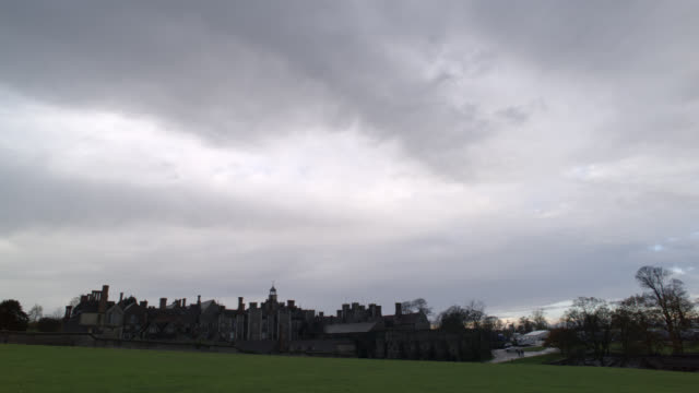 """pan right to left of stone buildings of castle, palace or fortress. grass field, lawn or meadow in fg. could be estate. rain. knole at sevenoaks in kent. countryside or rural area.<p><a href=""""https://www.sonypicturesstockfootage.com/footage?kid=4339"""">for - https stock videos & royalty-free footage"""