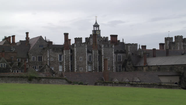 """wide angle of stone buildings with crenellation of castle, palace or fortress. grass field, lawn or meadow in fg. could be estate. chimneys. knole at sevenoaks in kent. countryside or rural area.<p><a href=""""https://www.sonypicturesstockfootage.com/footage - https stock videos & royalty-free footage"""