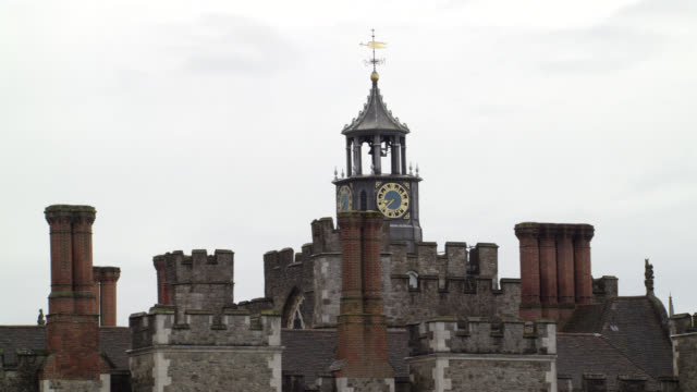 """WIDE ANGLE OF STONE BUILDINGS WITH CRENELLATION OF CASTLE, PALACE OR FORTRESS. CLOCK TOWER IN CENTER. CHIMNEYS. KNOLE AT SEVENOAKS IN KENT. COUNTRYSIDE OR RURAL AREA.<P><A HREF=""""HTTPS://WWW.SONYPICTURESSTOCKFOOTAGE.COM/FOOTAGE?KID=4339"""">FOR DAY-NIGHT MATC"""