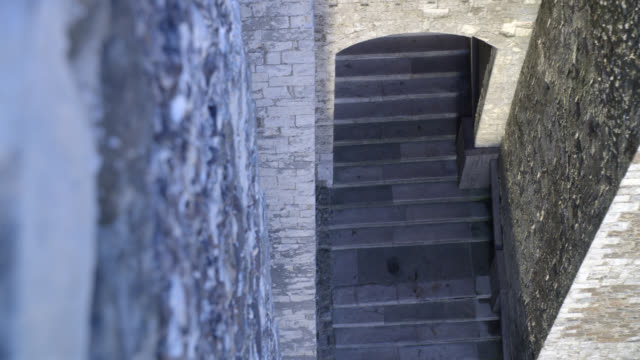 high angle down of stairs in stone building or castle. could be tower of london. actually dover castle in kent, england. - dover england stock videos and b-roll footage