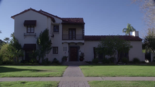 """wide angle of two story, middle to upper class spanish style house, villa or mansion with red tile roof and stucco. lawn, yard. los angeles area. matching dx/nx 4203-008 to 4203-009; 4203-058 to 4203-060.<p><a href=""""https://www.sonypicturesstockfootage.co%20-%20wide""""></a></p> stock videos & royalty-free footage"""