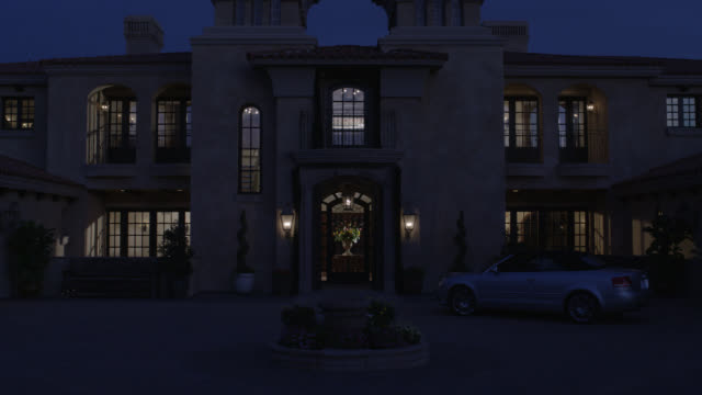 wide angle of two story, upper class spanish style house, villa or mansion with red tile roof and stucco. courtyard. los angeles area. audi convertible luxury car in driving away. interior lights brighten. los angeles area. matching dx/nx 4203-010 to 4203 - zweistöckiges bauwerk stock-videos und b-roll-filmmaterial