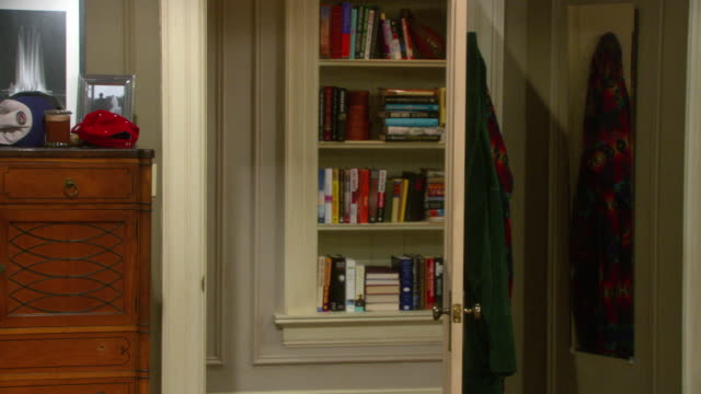 vídeos de stock, filmes e b-roll de medium angle of doorway to middle class bedroom in apartment. mirror on wall behind door. robes hang on door. books on wall shelf in hallway. dresser visible. - esetante de livro