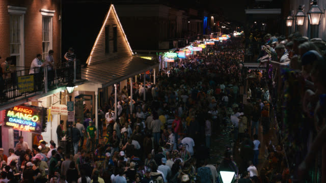 vídeos y material grabado en eventos de stock de high angle down of crowd of people on city street, could be bourbon street. mardi gras. party, celebration or festival. stores or shops, commercial area. people throwing beads from balconies. - mardi gras
