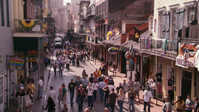 high angle down of people or pedestrians on city street, could be bourbon street. tourists. could be during mardi gras. stores or shops, commercial area. - new orleans mardi gras stock videos and b-roll footage